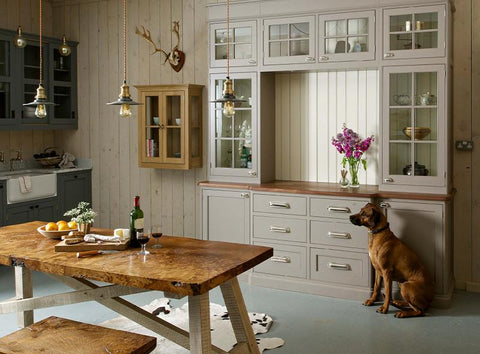 Neutral coloured kitchen interior with dog and trio of flat industrial pendants