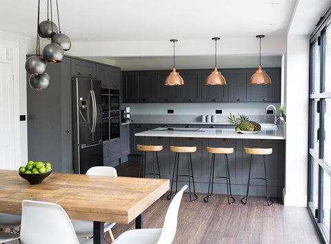 Grey open-plan kitchen interior with industrial lights