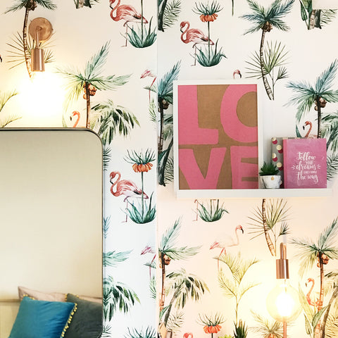 Tropical wall paper in an interior with vintage copper wall light and wall art