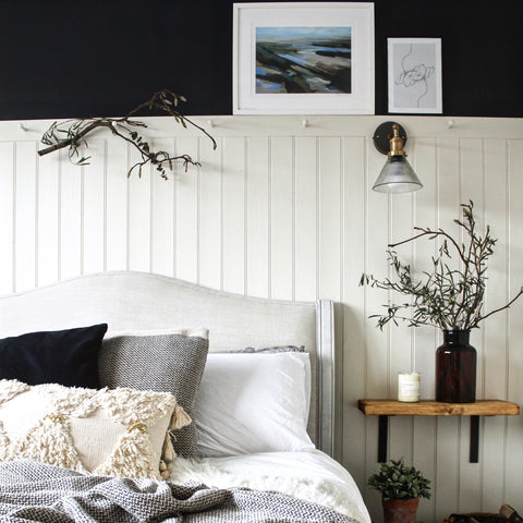 Rustic bedroom interior with panelled white wall