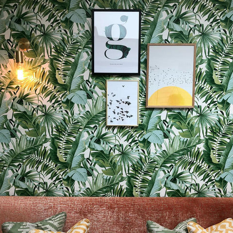 Tropical wallpaper with vintage wall light and wall art in a restaurant interior