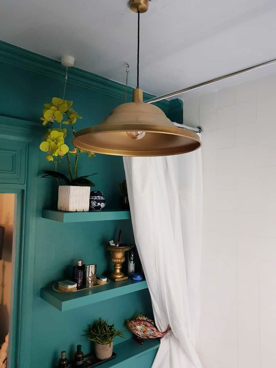 Emerald coloured walls paired with brass toned industrial lights