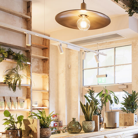 Avobar London cafe interior design with greenery and brass pendants