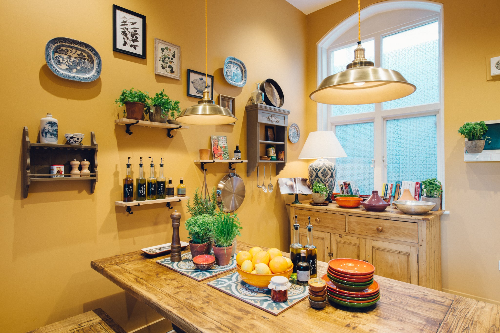 Yellow coloured kitchen with brass industrial lights