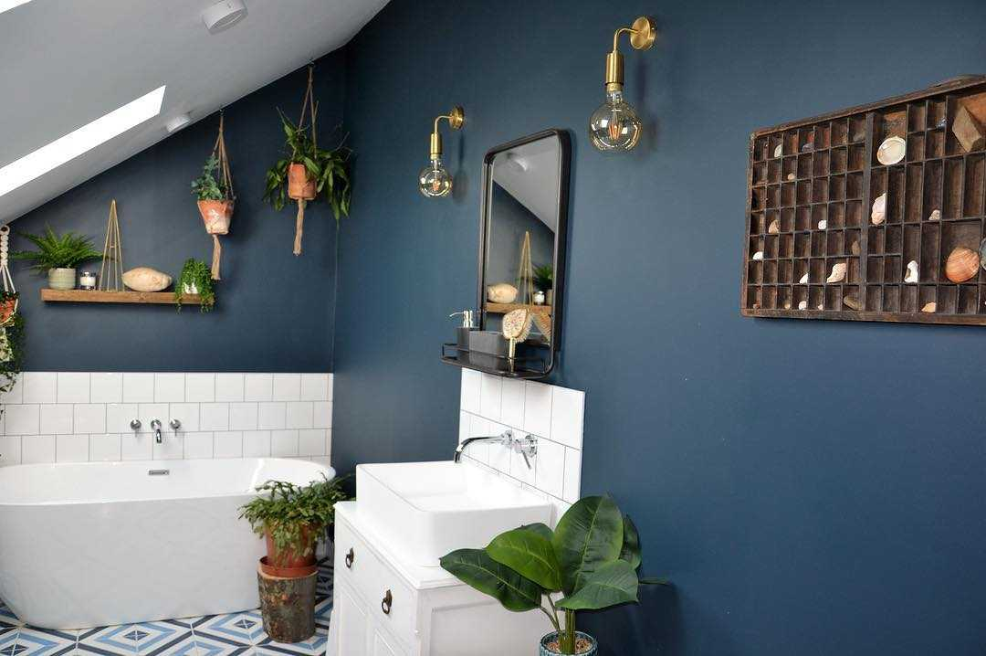 Blue bathroom interior with brass wall lights