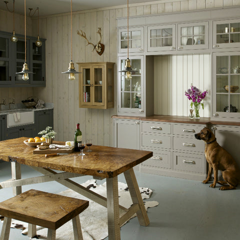 Neutral coloured kitchen interior with a wooden table and vintage lights