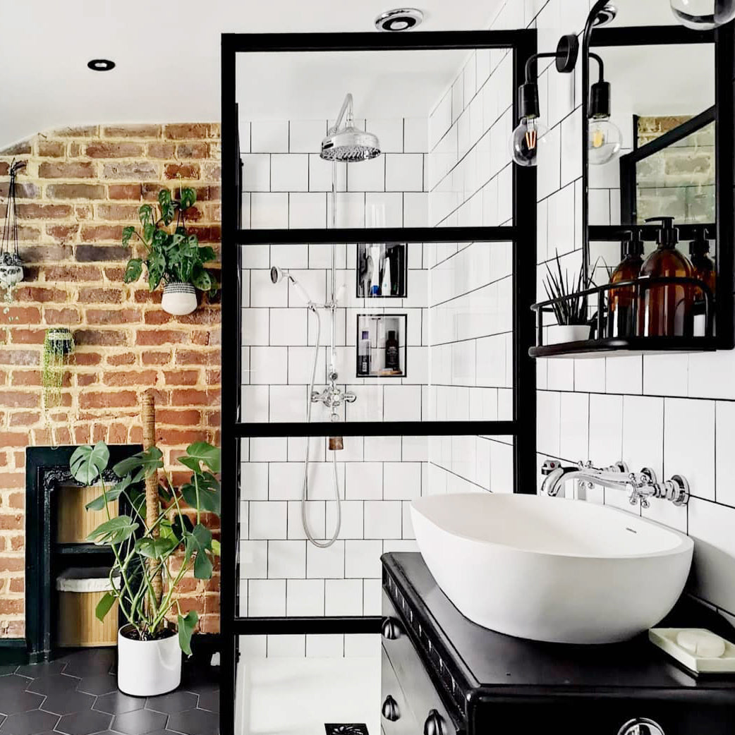 Industrial-style bathroom interior with exposed brick walls, tiles and vintage wall light