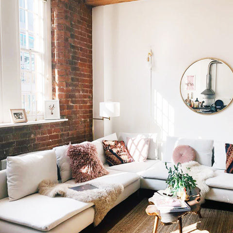 Industrial inspired living room decor with exposed brick wall and brass wall light