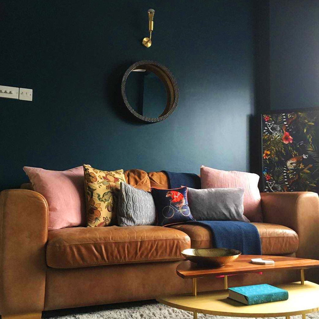 Living room interior with dark blue walls and brass wall light
