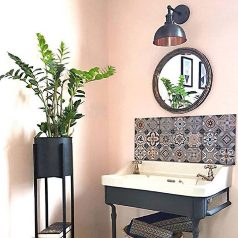 Pink bathroom decor with standing plant, patterned splashback tiles and vintage wall light