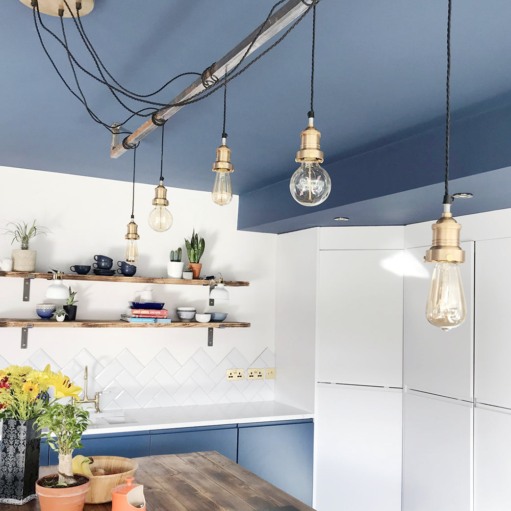 Modern kitchen interior design with blue walls and hanging industrial brass lights