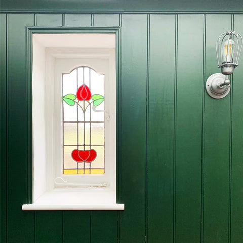 Green panelled wall with stained glass window and industrial wall light