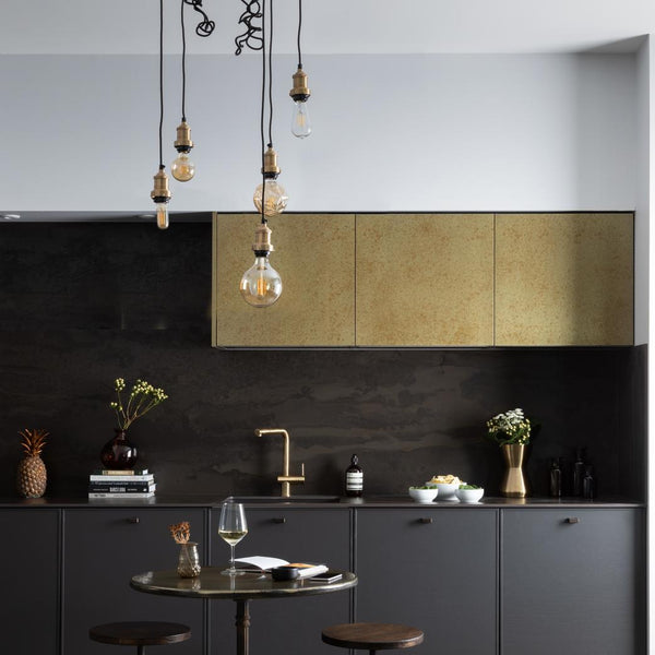 A dark industrial style kitchen with exposed wire lights