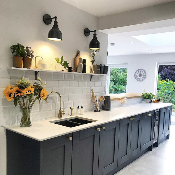 A kitchen with black cabinets and industrial wall lights