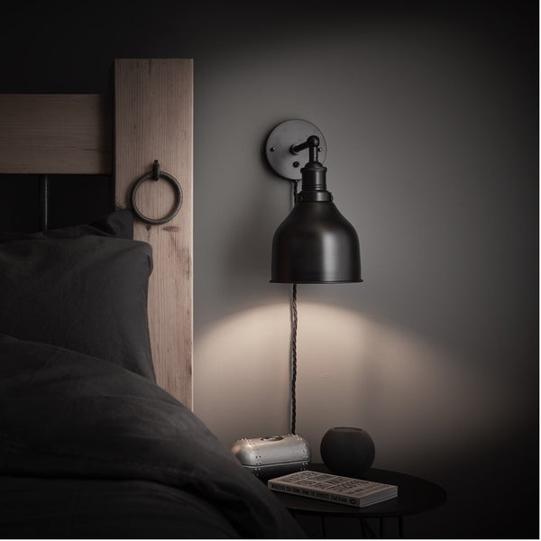 A black cone wall light shining over a bedroom side table