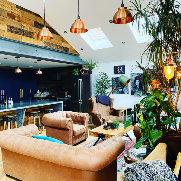 Leather sofas and pendant lights in an open living room