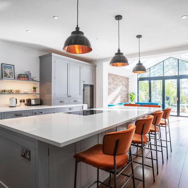 A modern, open kitchen with metal pendants