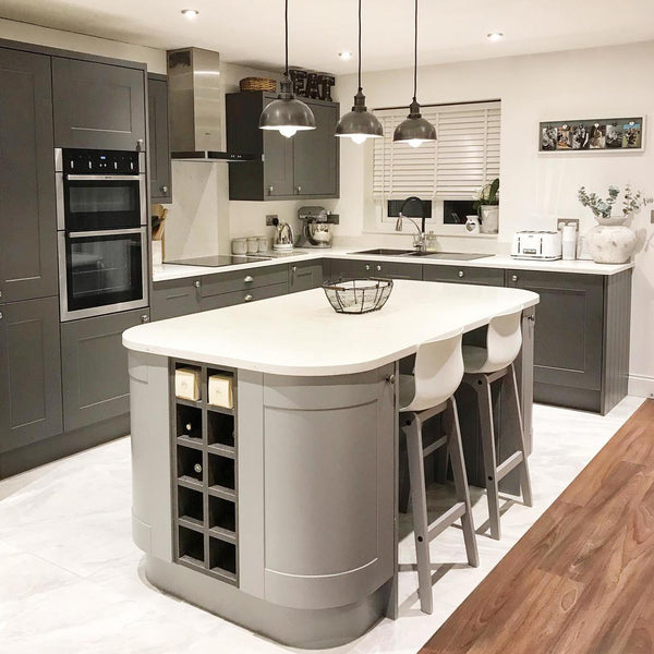 A grey industrial kitchen with with hanging pendants