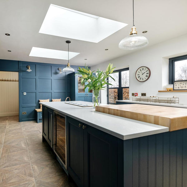 A kitchen with blue cabinets and glass pendants