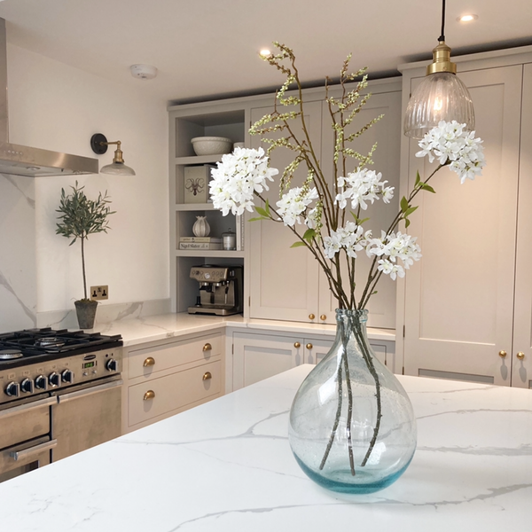 A white kitchen with a vase of flowers