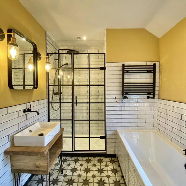 A bright bathroom with yellow walls and patterned tiles