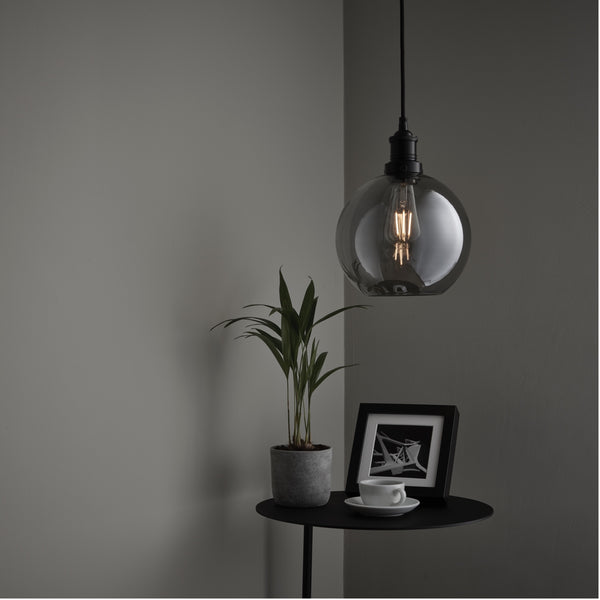 A glass globe pendant hanging over a table