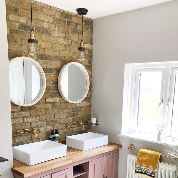 Pink bathroom interior with duo of mirrors and pendants