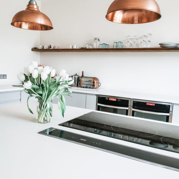 A white kitchen with brass light pendants
