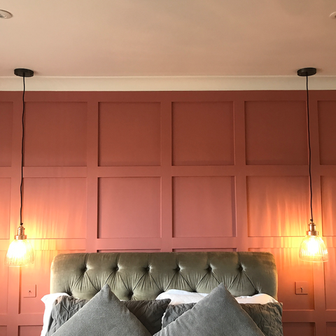 A bedroom with a pink wall and hanging lights