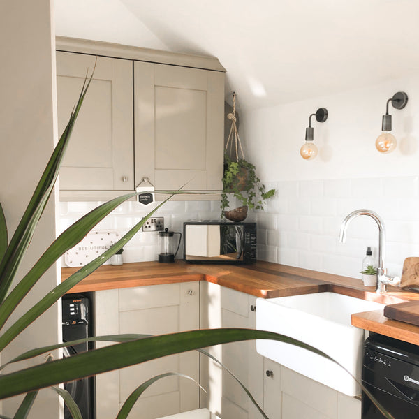 A small but open kitchen with wall lights