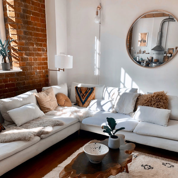 A white living room with faux fur throws and cushions