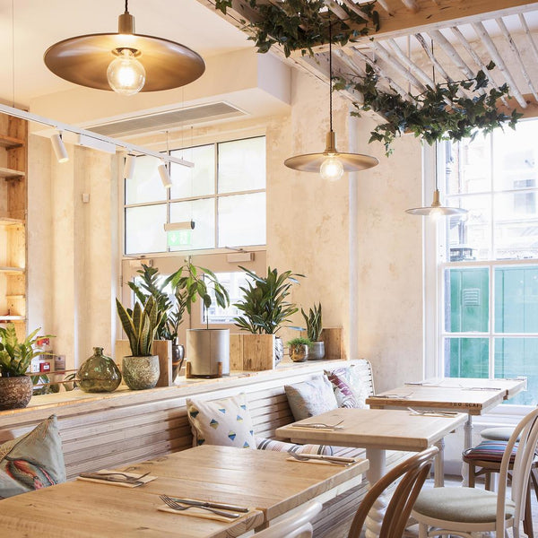 Flat pendant lights hanging over a dining area in a hotel restaurant