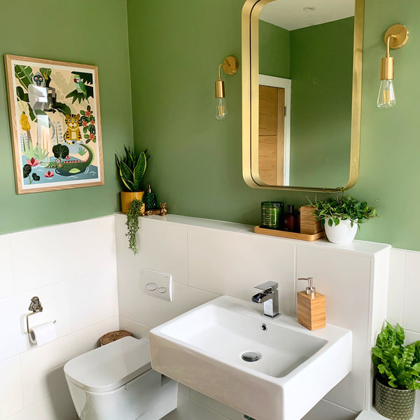 An art deco bathroom with brass furniture and green walls