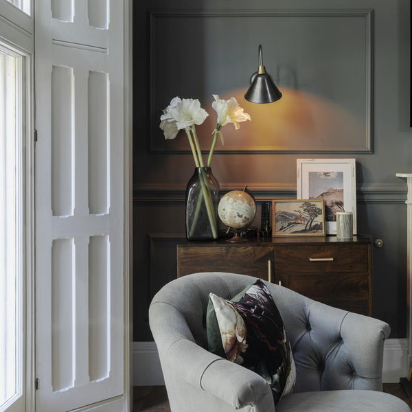 An armchair by a window and lit by a wall light