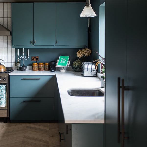 A modern kitchen with green cupboards and glass lighting by Industville