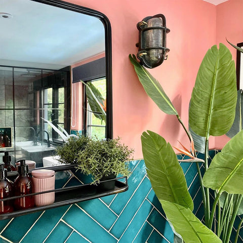 A pink and blue bathroom with antique-style mirror