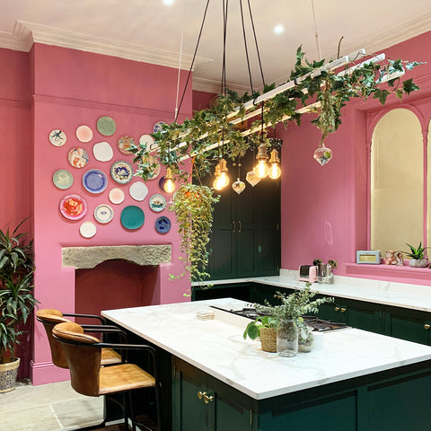 A pink kitchen with decorative plates on the wall and hanging plants