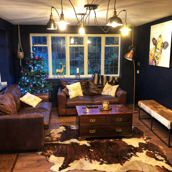 A cosy living room with leather sofa and hanging industrial lighting