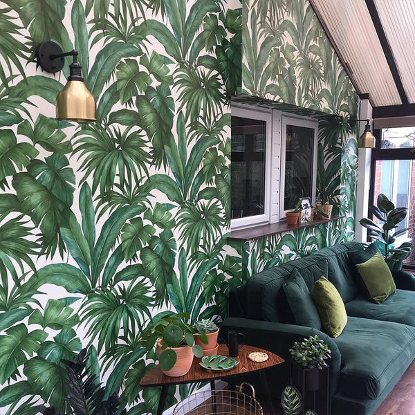 A green living room interior with floral wallpaper