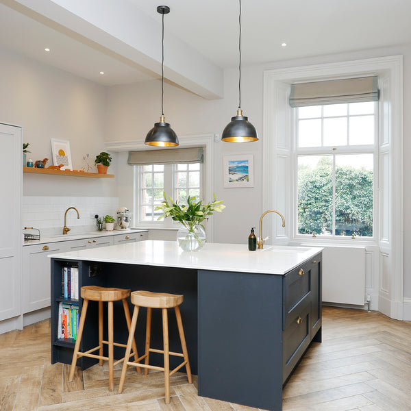 A contemporary kitchen with hanging metal lights by Industville