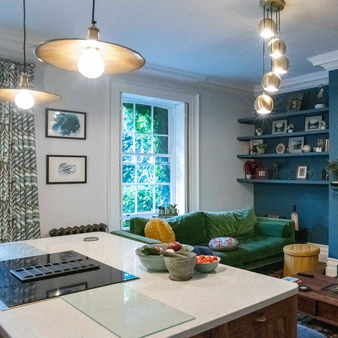An open plan kitchen and living space with different style lighting