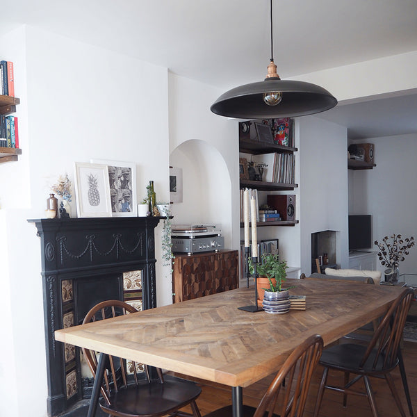 A traditional dining room with oversized industrial lighting