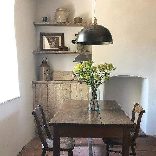 A rustic dining room with wooden table and industrial light by Industville