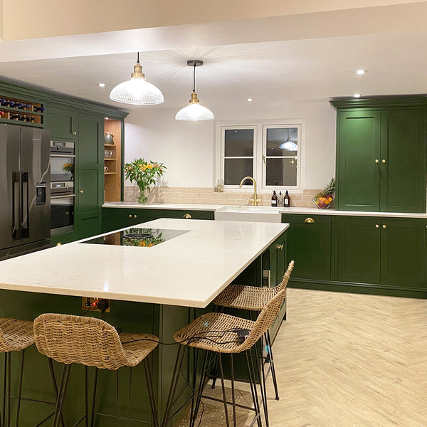 A green modern kitchen with glass lighting