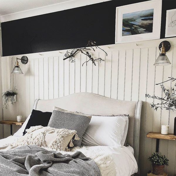 A rustic bedroom with wooden wall panels and glass lighting by Industville