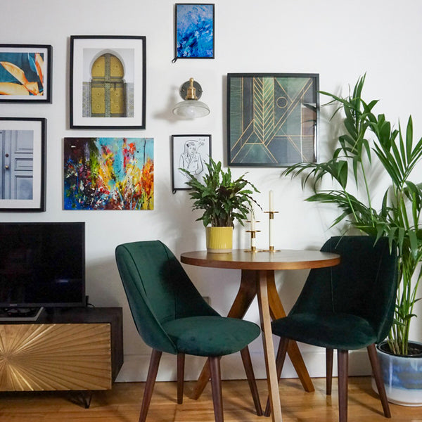 A maximalist interior design with green chairs and picture frames