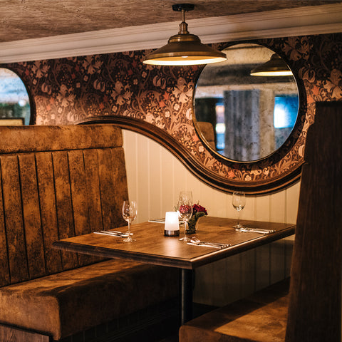 A wooden restaurant interior with industrial hanging lights by Industville