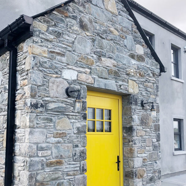 Grey brick building with a yellow front door and pewter industrial outdoor wall lights