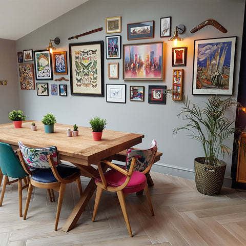 A dining table by a gallery wall