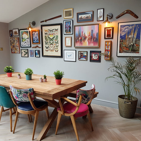 A colourful dining room with hanging pictures and metal lighting